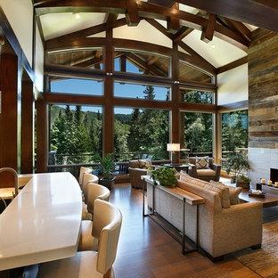 Exempel på ett stort amerikanskt allrum med öppen planlösning, med vita väggar, ljust trägolv, en standard öppen spis, en spiselkrans i sten och ett finrum