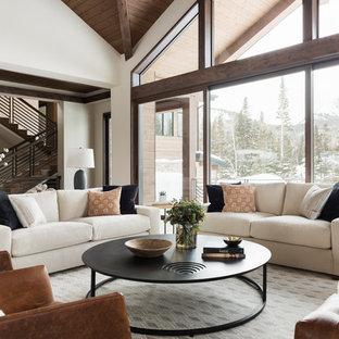 Idee per un grande soggiorno contemporaneo aperto con angolo bar, pareti beige, pavimento in legno massello medio, camino classico, cornice del camino in pietra e pavimento beige