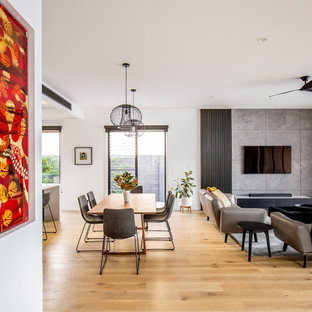 Design ideas for a contemporary open concept living room in Gold Coast - Tweed with white walls, medium hardwood floors, no fireplace, a wall-mounted tv and brown floor.