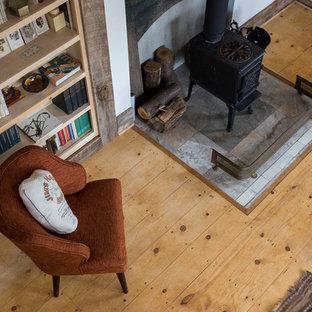 Ispirazione per un piccolo soggiorno country aperto con pareti bianche, parquet chiaro, stufa a legna, cornice del camino in cemento e nessuna TV