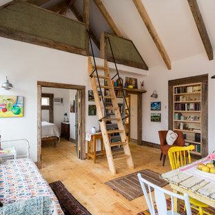 Ispirazione per un piccolo soggiorno country stile loft con libreria, pareti bianche, parquet chiaro, stufa a legna, cornice del camino in cemento e nessuna TV