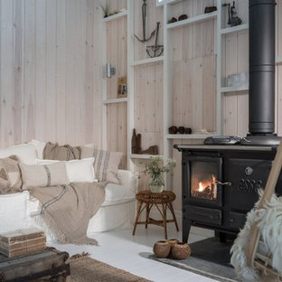 コーンウォールのカントリー風おしゃれな独立型リビング (ベージュの壁、塗装フローリング、薪ストーブ、金属の暖炉まわり、白い床) の写真