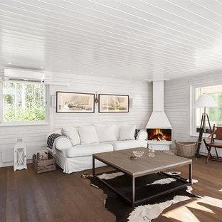 Imagen de salón abierto, campestre, de tamaño medio, con paredes blancas, chimenea de esquina, televisor colgado en la pared, suelo de madera oscura y marco de chimenea de metal