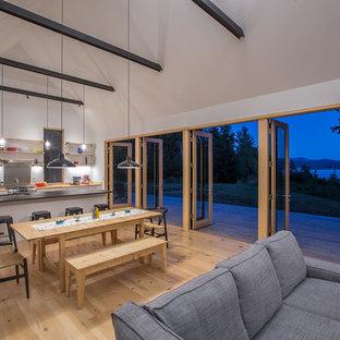 Foto de salón abierto, rural, pequeño, con paredes blancas, suelo de madera clara, estufa de leña y marco de chimenea de baldosas y/o azulejos