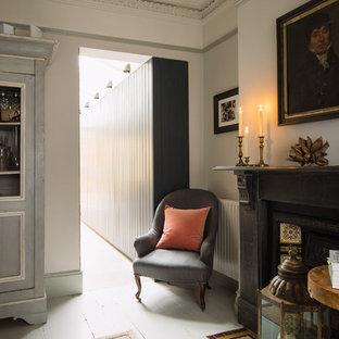 ロンドンの中サイズのトラディショナルスタイルのおしゃれなリビング (グレーの壁、塗装フローリング、標準型暖炉、木材の暖炉まわり、白い床) の写真