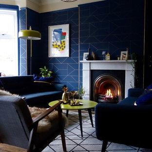 Idée de décoration pour un salon design de taille moyenne et fermé avec un mur bleu, un sol en bois foncé, une cheminée standard, un manteau de cheminée en pierre et aucun téléviseur.