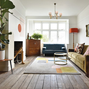 Design ideas for a medium sized eclectic open plan living room in London with white walls, a concealed tv, medium hardwood flooring, a standard fireplace and brown floors.
