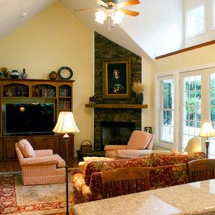 Idee per un soggiorno american style di medie dimensioni e chiuso con pareti gialle, pavimento in legno massello medio, camino ad angolo, cornice del camino in pietra e TV autoportante