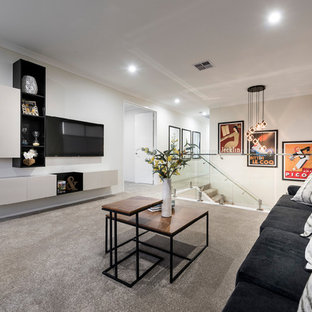 This is an example of a large contemporary loft-style living room in Perth with white walls, a wall-mounted tv, beige floor and carpet.