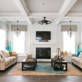 ジャクソンビルの中サイズのビーチスタイルのおしゃれなLDK (白い壁、セラミックタイルの床、標準型暖炉、木材の暖炉まわり、壁掛け型テレビ) の写真