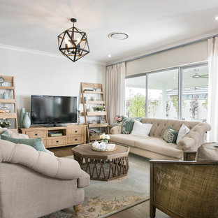 This is an example of a beach style living room in Perth with grey walls, medium hardwood floors and a freestanding tv.
