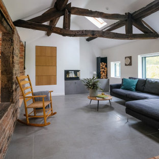 This is an example of a medium sized farmhouse open plan living room in West Midlands with white walls, concrete flooring, a corner fireplace, a plastered fireplace surround, grey floors, a vaulted ceiling and brick walls.
