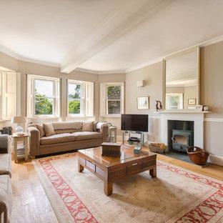 Diseño de salón para visitas cerrado, campestre, grande, con paredes beige, suelo de madera en tonos medios, chimenea tradicional, marco de chimenea de yeso y televisor en una esquina