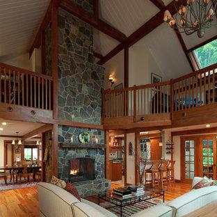 Idée de décoration pour un grand salon mansardé ou avec mezzanine tradition avec un mur beige, un sol en bois brun, une cheminée standard et un manteau de cheminée en pierre.