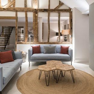 Idee per un grande soggiorno country aperto con pareti bianche, pavimento in pietra calcarea, camino bifacciale, cornice del camino in metallo e pavimento bianco