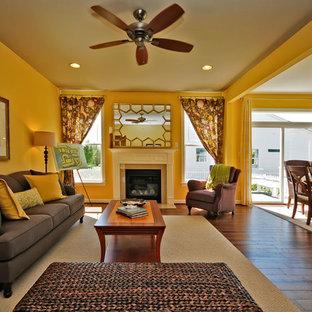 他の地域のビーチスタイルのおしゃれなリビング (黄色い壁、濃色無垢フローリング、標準型暖炉) の写真