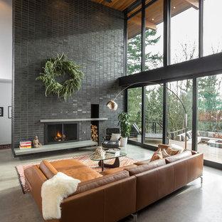 ポートランドの大きいミッドセンチュリースタイルのおしゃれなリビング (白い壁、コンクリートの床、標準型暖炉、レンガの暖炉まわり、テレビなし、グレーの床) の写真