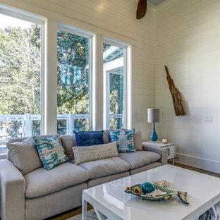 マイアミの巨大なビーチスタイルのおしゃれなLDK (白い壁、無垢フローリング、横長型暖炉、石材の暖炉まわり、テレビなし、茶色い床) の写真