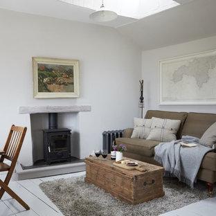 Esempio di un soggiorno country di medie dimensioni e chiuso con sala formale, pareti bianche, pavimento in legno verniciato, stufa a legna, cornice del camino in intonaco e pavimento bianco