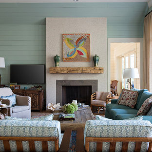 チャールストンの中サイズのトラディショナルスタイルのおしゃれな独立型リビング (青い壁、標準型暖炉、コンクリートの暖炉まわり、壁掛け型テレビ) の写真