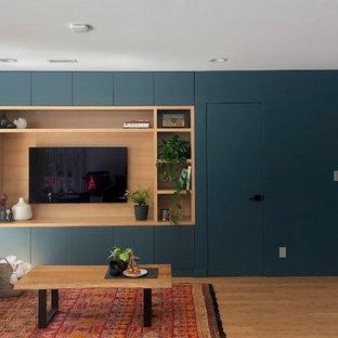 Idéer för att renovera ett mellanstort funkis allrum med öppen planlösning, med ett finrum, blå väggar, bambugolv, en inbyggd mediavägg och brunt golv