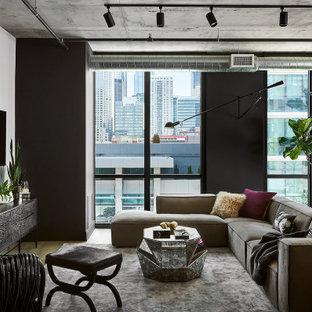 Idee per un grande soggiorno industriale stile loft con pareti nere e TV a parete