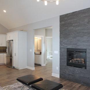 Foto di un soggiorno design di medie dimensioni e aperto con sala formale, pareti grigie, pavimento in laminato, camino classico e cornice del camino in pietra