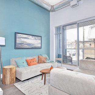 Ejemplo de salón abierto, actual, pequeño, con paredes azules, suelo de madera en tonos medios y televisor colgado en la pared