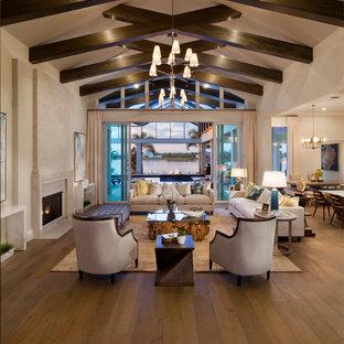 Idéer för att renovera ett mycket stort vintage allrum med öppen planlösning, med ett finrum, beige väggar, mellanmörkt trägolv, en standard öppen spis, en spiselkrans i sten och brunt golv