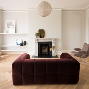 Contemporary formal open plan living room in London with beige walls, light hardwood flooring, a wood burning stove, a metal fireplace surround and beige floors.