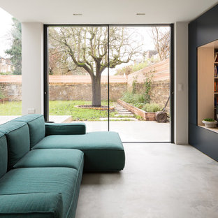 Contemporary formal open plan living room in London with white walls, concrete flooring, a built-in media unit and grey floors.