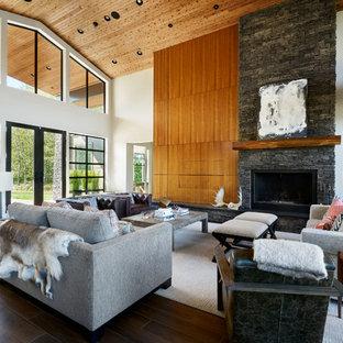 Modelo de salón abierto, actual, con chimenea lineal, marco de chimenea de piedra, televisor retractable, suelo marrón y paredes grises