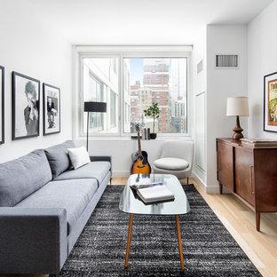 Trendy light wood floor and beige floor living room photo in New York with white walls