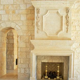 ローリーの広いトラディショナルスタイルのおしゃれな独立型リビング (ライブラリー、ベージュの壁、ライムストーンの床、標準型暖炉、石材の暖炉まわり) の写真