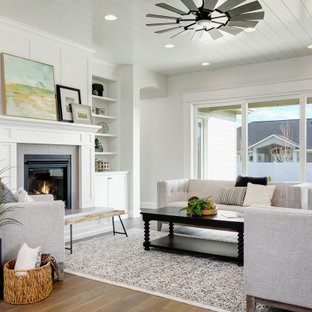 This is an example of a large transitional formal living room in Boise with white walls, a standard fireplace, a plaster fireplace surround, no tv, brown floor and timber.