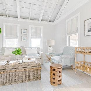 Ejemplo de salón abierto, costero, pequeño, con paredes beige, suelo de madera clara y suelo beige