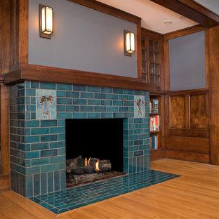 Foto di un soggiorno american style di medie dimensioni e aperto con libreria, pareti grigie, pavimento con piastrelle in ceramica, camino classico, cornice del camino piastrellata, nessuna TV e pavimento blu