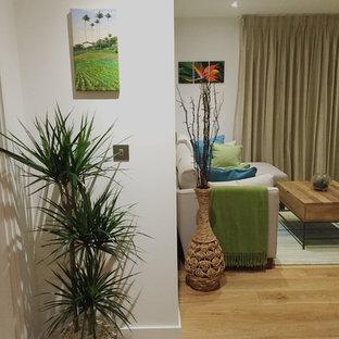 ロンドンの小さいトロピカルスタイルのおしゃれなLDK (白い壁、無垢フローリング、暖炉なし、据え置き型テレビ) の写真