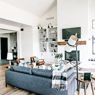 Modelo de salón para visitas abierto, campestre, de tamaño medio, con paredes blancas, suelo de madera en tonos medios, chimenea tradicional, marco de chimenea de ladrillo, televisor colgado en la pared y suelo marrón