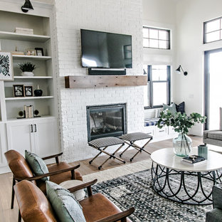 Design ideas for a medium sized country formal open plan living room in Salt Lake City with white walls, medium hardwood flooring, a standard fireplace, a brick fireplace surround, a wall mounted tv and brown floors.