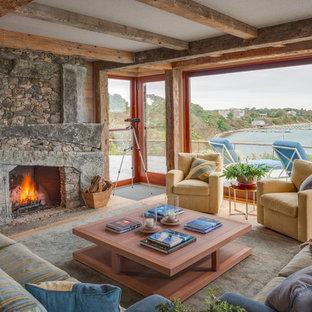 Ejemplo de salón para visitas abierto, rural, sin televisor, con suelo de madera clara, chimenea tradicional, paredes marrones y marco de chimenea de piedra