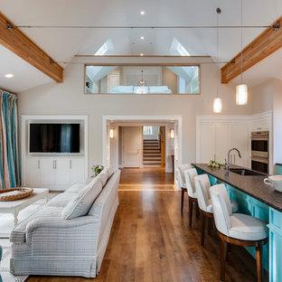 Modelo de salón para visitas abierto, actual, de tamaño medio, sin chimenea, con televisor colgado en la pared, paredes beige y suelo de madera oscura