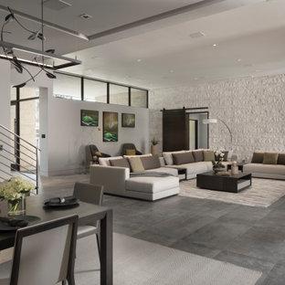 Idee per un ampio soggiorno contemporaneo aperto con pareti multicolore, pavimento in gres porcellanato, camino bifacciale, cornice del camino in mattoni, TV a parete e pavimento grigio