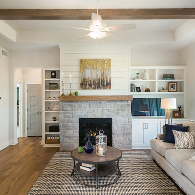 Mid-sized farmhouse open concept medium tone wood floor living room photo in Wichita with white walls, a standard fireplace and a stone fireplace