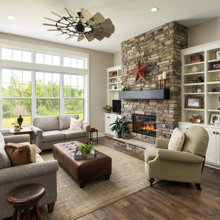 グランドラピッズの中サイズのカントリー風おしゃれなLDK (ベージュの壁、標準型暖炉、埋込式メディアウォール、茶色い床、ラミネートの床、石材の暖炉まわり) の写真