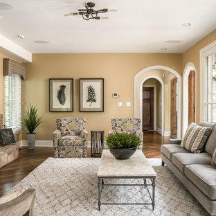 Diseño de salón tradicional con paredes marrones, suelo de madera oscura, chimenea tradicional, marco de chimenea de piedra y suelo marrón