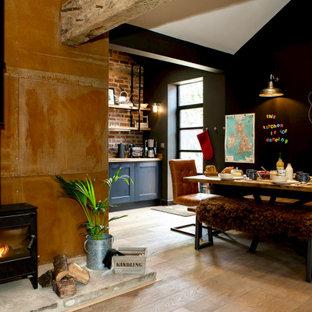 Mittelgroßes, Offenes Eklektisches Wohnzimmer mit schwarzer Wandfarbe, braunem Holzboden, Kaminofen, Kaminumrandung aus Metall, Wand-TV, braunem Boden, gewölbter Decke und Ziegelwänden in Sonstige