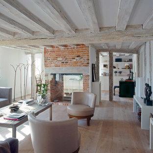 Ejemplo de salón abierto, actual, de tamaño medio, sin televisor, con paredes blancas, suelo de madera clara, chimenea de doble cara y marco de chimenea de ladrillo