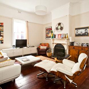 Foto di un piccolo soggiorno boho chic chiuso con parquet scuro, camino classico, TV autoportante e pareti bianche