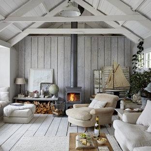 コーンウォールの大きいカントリー風おしゃれなリビング (白い壁、塗装フローリング、薪ストーブ、木材の暖炉まわり、白い床) の写真